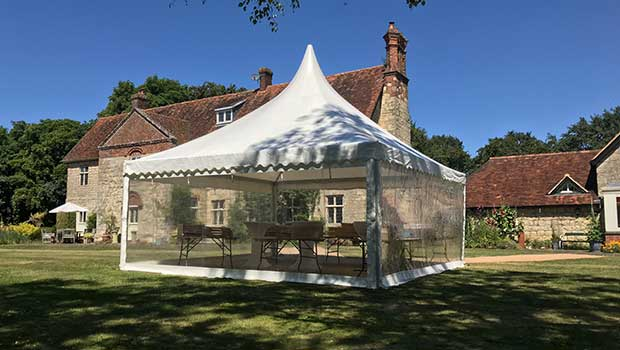 Pavilion marquee with clear walls and seating in private garden